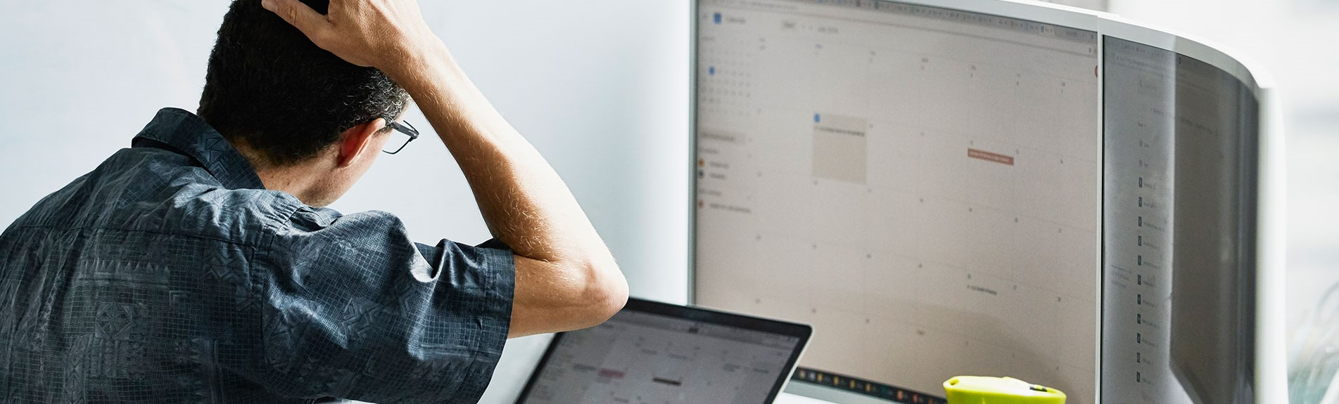 Man Scratching Head While Looking At Calendar On Computer Monitor