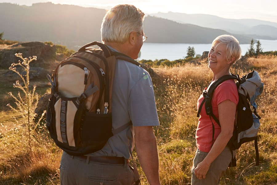 Senior Couple Walking On Top Of Hill On Hike Through Countryside
