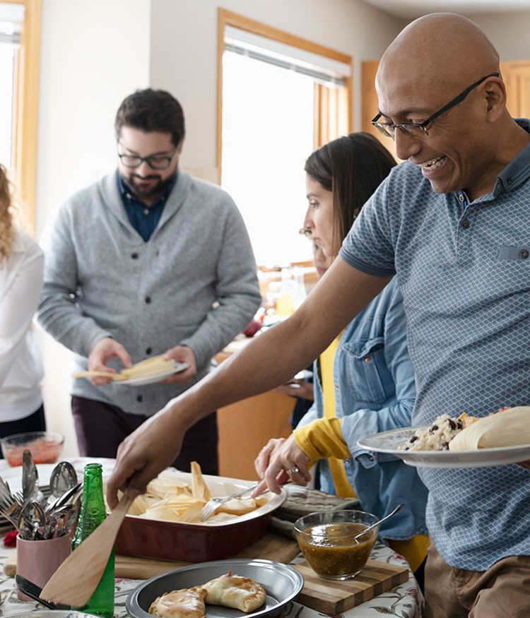 Latinx Family Enjoying Buffet Dinner In Kitchen