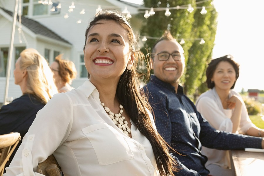 Smiling Woman Enjoying Garden Party At Sunny Patio Table