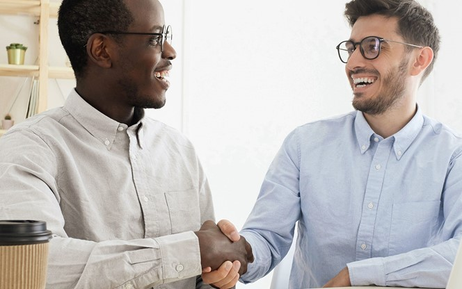 Young multiethnic men in smart casual wear shaking hands while working together