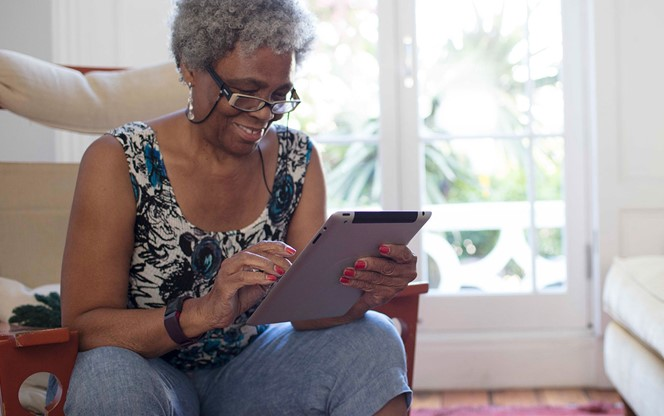Senior Woman Using Digital Tablet Living Room