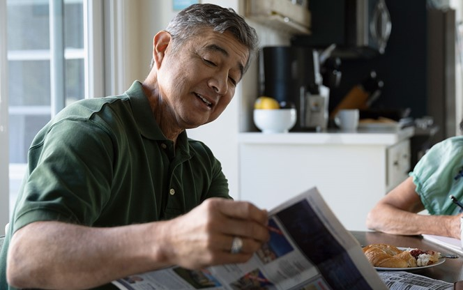 Latinx Senior Couple Reading Newspaper And Eating Breakfast At Kitchen Table