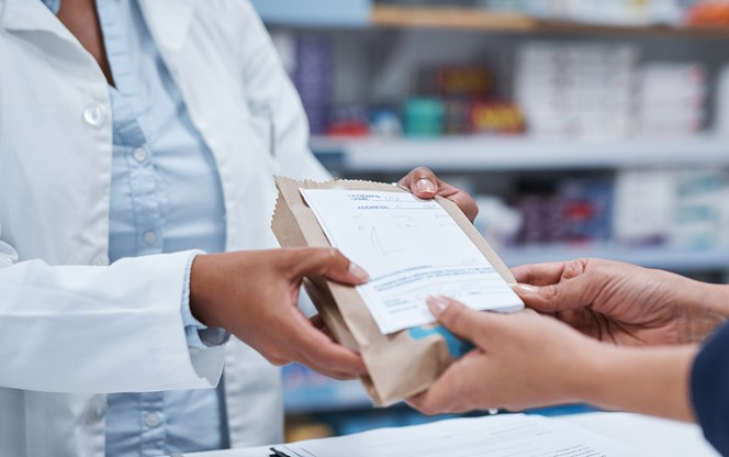 Pharmacist Giving Prescription Drug To Customer