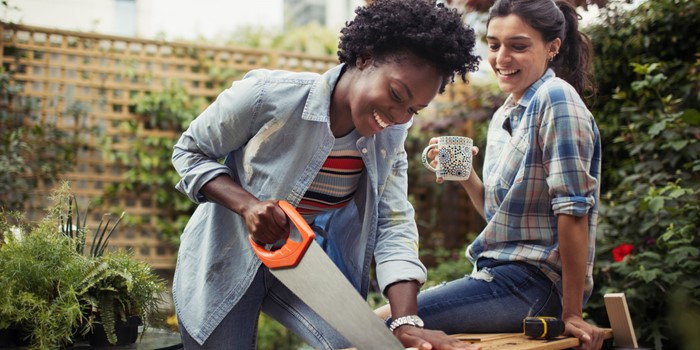 Women Drinking Coffee And Cutting Wood With Saw On Patio