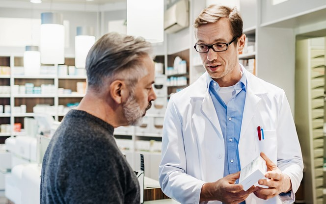 Pharmacist advising customer on medicine instructions