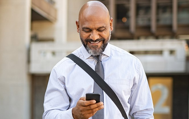 Satisfied Businessman Walking While Using Phone