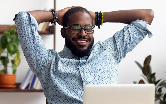 Young Black Man With Laptop Relaxed And Feeling No Stress