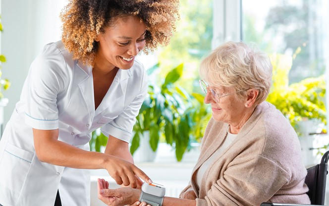 Home Carer Checking Blood Pressure Of Elderly Lady