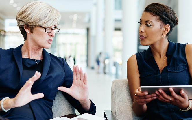 Two Businesswomen Having A Discussion Together While Being Seated Inside Of A Office Building During The Day