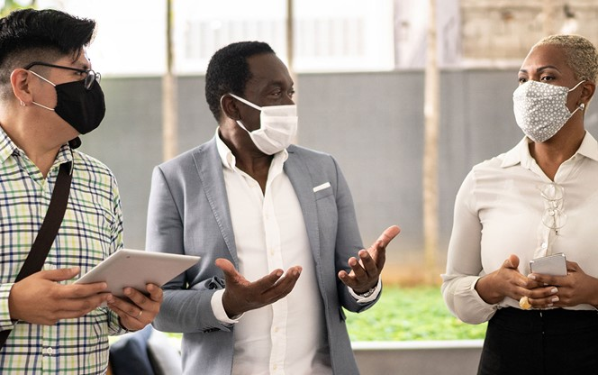Coworkers Walking And Talking At Offices Lobby With Face Mask
