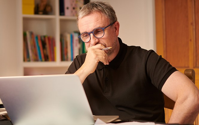 Mature Man Working On His Laptop From Home Looking Concerned