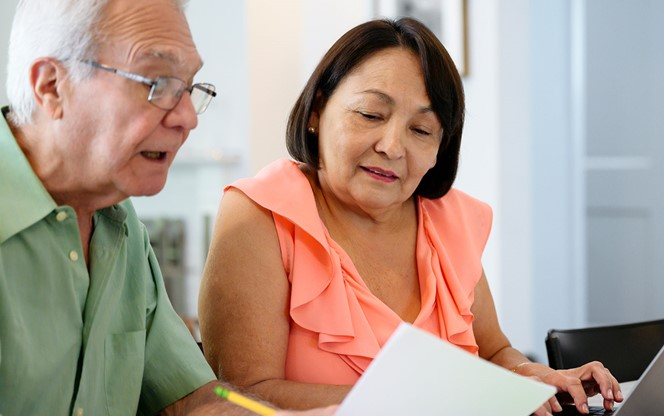Hispanic Senior Couple Using Laptop To Organize Financial Planning