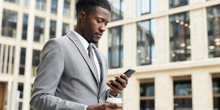 Serious African Businessman In Suit Drinking Coffee And Reading A Message On His Mobile Phone While Walking In The City