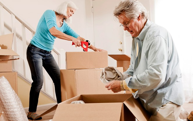Senior Couple Boxing Their Furniture And Preparing For A Move