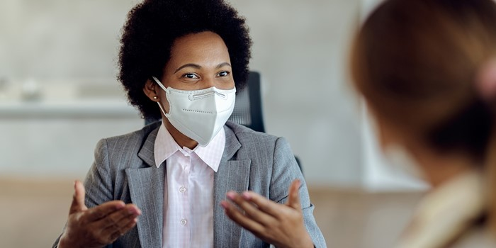 Black Female Financial Consultant Talking To Her Client And Wearing Protective Face Mask During The Meeting