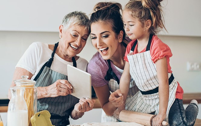 Grandmother Daughter And Grand Daughter With Digital Tablet Preparing Cookies Together