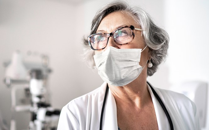 Senior Female Doctor At Hospital Using Protective Mask
